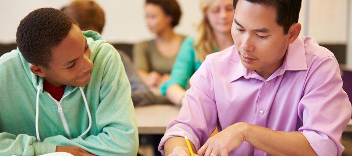 High School Teacher Helping Student With Written Work