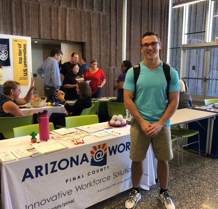 Photograph of a participant attending a Job Fair standing by an ARIZONA@WORK table