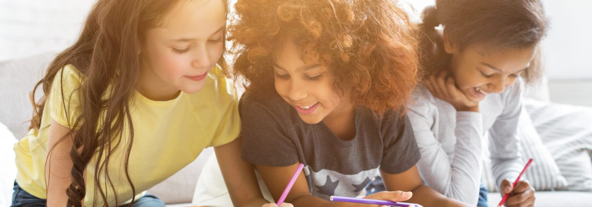 Multiethnic girls drawing at table with colorful pencils