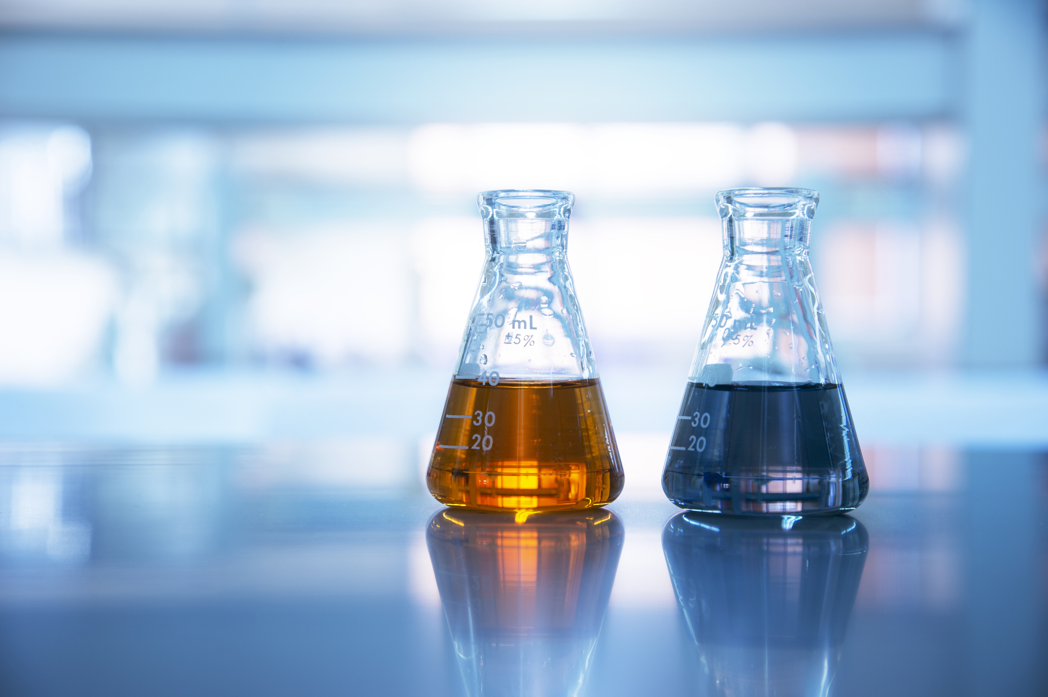 two glass flasks with orange and black solution in chemical science  laboratory background - Central Arizona College