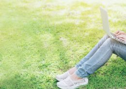 Girl on computer sitting in grass - summer online classes