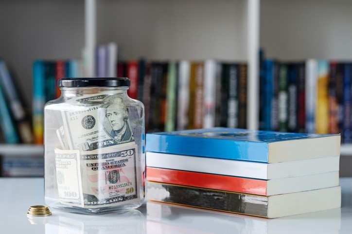 Jar of money next to stack of books