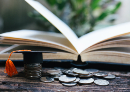 open book with coins and graduation cap